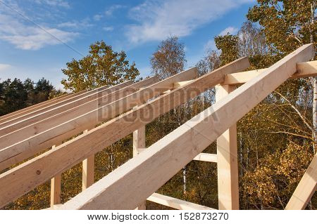 Roof beams. Sunny autumnal evening at the construction site of a wooden house. Unfinished house.