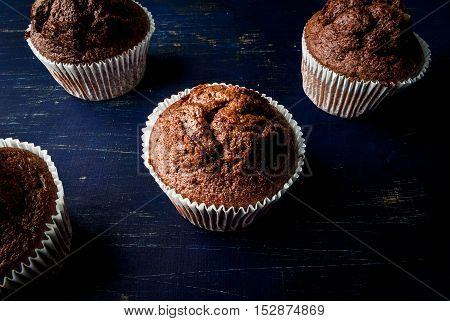 Freshly baked chocolate muffins with lemon kurd inside, on a dark blue wooden table.  Copy space