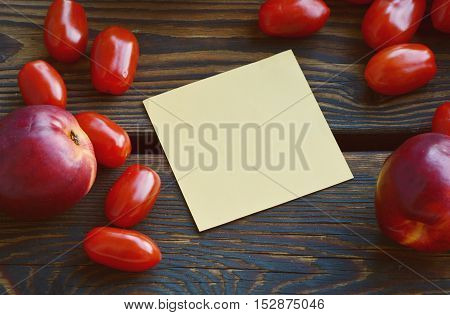 empty yellow paper with tomatoes and nectarines arround on a wooden floor