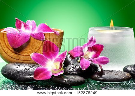 Spa concept, orchid, candle, oil and stone on green background
