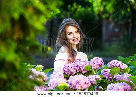 young sexy woman or girl with long brunette hair and red lips on pretty smiling face in blooming bush of hydrangea flowers violet and pink color outdoor on natural background in garden