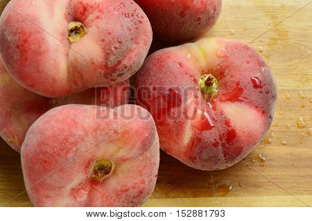 Dough nut peaches also known as Saturn peach with water drop on wooden board.
