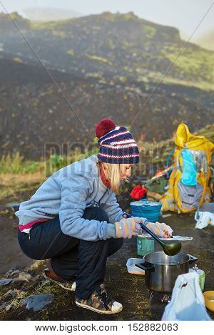 woman hiker cooking outdoor in camping, Iceland