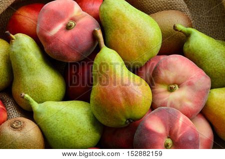 Dough nut peach, European Pear, Kiwifruit, nectarines on sack cloth background.