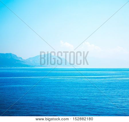 Beautiful Blue Sea with Sky and White Clouds. Mountain Silhouettes in Haze on the Horizon. Summer Seascape with Clear Water. Serene Ocean and Tranquility Concept. Copy Space Background. Toned Photo.