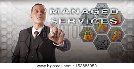 Manager with assertive and perky look is activating MANAGED SERVICES onscreen. Business concept and information technology metaphor for outside handling of IT via automated professional services.