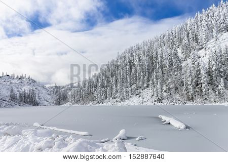 Beautiful lake Amut in taiga hills on Far East of Russia in early october. Mountain lake in winter. Beautiful nature. Snowy weather.