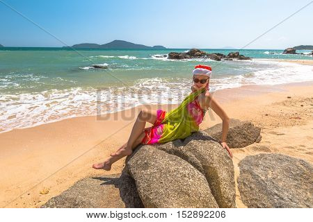 Christmas in the tropical beach. Fashionable woman with red Santa Claus hat relaxing on rocks in Laem Ka Beach for the Christmas holidays in Phuket, Thailand.