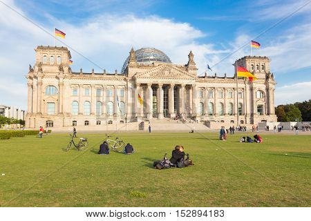 Berlin, Germany - Sep 9, 2016: Young couple kissing on a meadow infront of german parliament Reichstag building on Septgember 9th, 2016 in Berlin, Germany.