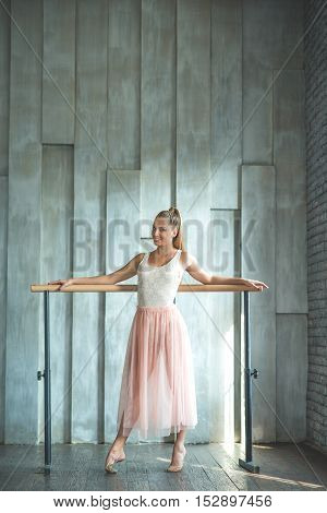 Forget troubles and just dance. Full length photo of graceful ballerina posing while standing and holding her hands on ballet barre