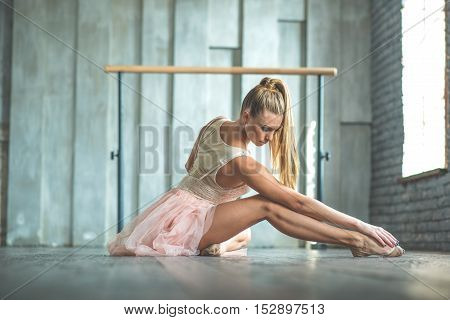 Never miss chance to dance. Beautiful ballerina sitting on floor in studio with closed eyes against barre on background