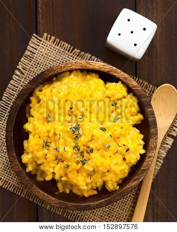 Pumpkin risotto prepared with pumpkin puree and sprinkled with fresh thyme leaves served in wooden bowl photographed overhead with natural light (Selective Focus Focus on the top of the risotto)