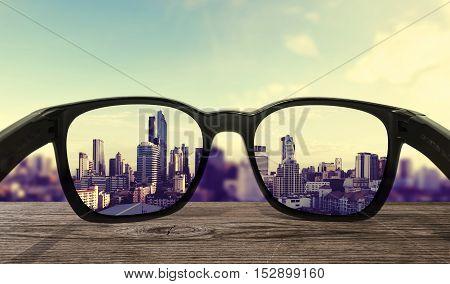 Sun glasses on wooden desk, focused on lens city view