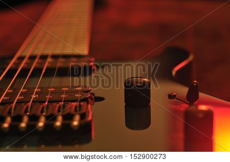 Closeup of electric guitar strings with bright red and orange lights
