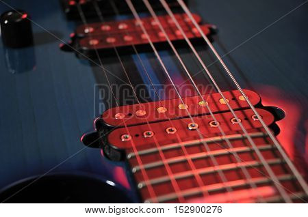 Closeup detail of Electric guitar strings with red light