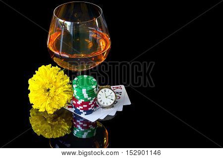 Poker cards with colorful chips and snifter with wrist watch
