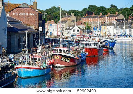 WEYMOUTH, UNITED KINGDOM - JULY 18, 2016 - Elevated view of the fishing trawlers in the harbour and quayside buildings Weymouth Dorset England UK Western Europe, July 18, 2016.