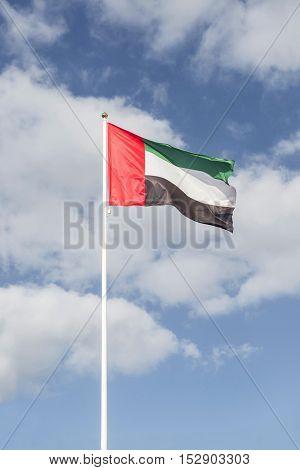 National flag of United Arab Emirates. Hoisted against bright blue sky.
