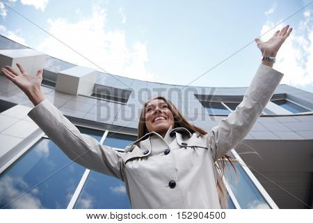 Woman is standing near modern building with her arms raised.Low Angle View