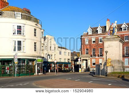 WEYMOUTH, UNITED KINGDOM - JULY 19, 2016 - Shops at the end of the Esplanade with The Kings statue to the right hand side monument to King George III Weymouth Dorset England UK Western Europe, July 19, 2016.