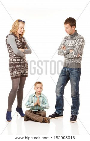 Family Misunderstanding.FatherMother and Son on the White Background. Son Sits in Meditation Pposeand his Parents Stand near and Dont Know What to Do.