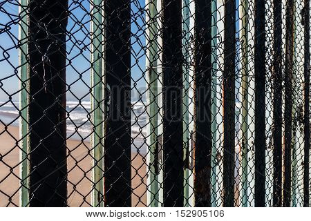 Close-up view of the border fence separating San Diego, California and Tijuana, Mexico, with a view of the beach on the Mexico side in the background.
