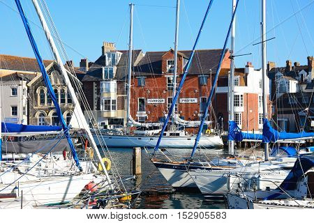 WEYMOUTH, UNITED KINGDOM - JULY 19, 2016 - Yachts and fishing boats in the harbour with the Harbour Master office to the rear Weymouth Dorset England UK Western Europe, July 19, 2016.