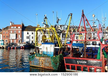 WEYMOUTH, UNITED KINGDOM - JULY 19, 2016 - View of fishing trawlers in the harbour with quayside buildings to the rear Weymouth Dorset England UK Western Europe, July 19, 2016.