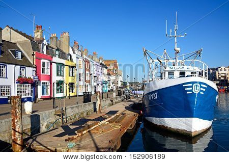 WEYMOUTH, UNITED KINGDOM - JULY 19, 2016 - Fishing trawler moored in the harbour with quayside buildings to the left Weymouth Dorset England UK Western Europe, July 19, 2016.