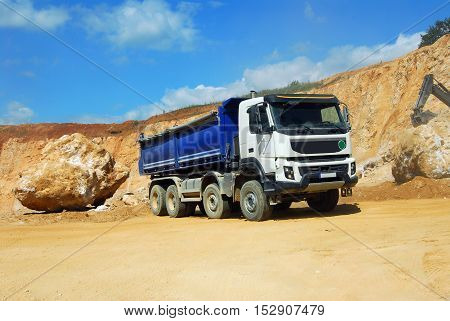 large dump truck driving in the dust in the quarry