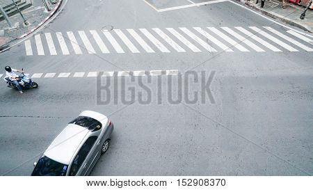 street on the top view with the crosswalk sign on the road and car and motocycle (Aerial photo)