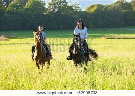 Horseback Riding Lessons - Woman Riding along a Boy on a Horse