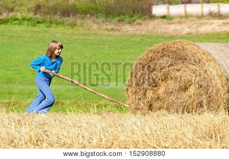 Boy Moving Bale of Hay with Stick as a Lever