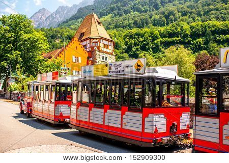 Vaduz, Liechtenstein - July 01, 2016: People on the tourist train visit famous red house with wineyard in Vaduz city. This house is very popular tourist attraction in Liechtenstein