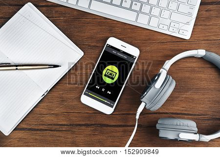 Smartphone and earphones on wooden table, closeup. Music player interface on screen.