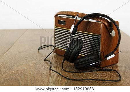 Headphones and old vintage radio on wooden surface