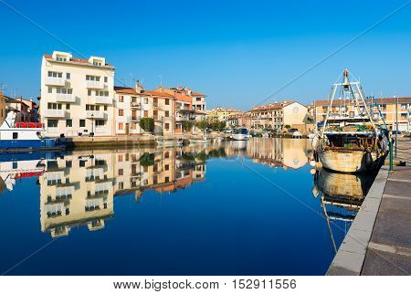 Grado - December 2015, Italy: Colored houses and boats with their reflections in water of one of the canals of Grado
