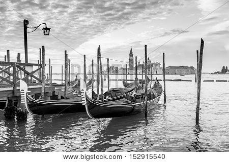 Black and white photo of gondolas moored by Saint Mark square in sunrise. San Giorgio di Maggiore church is in the background (Venice Italy)