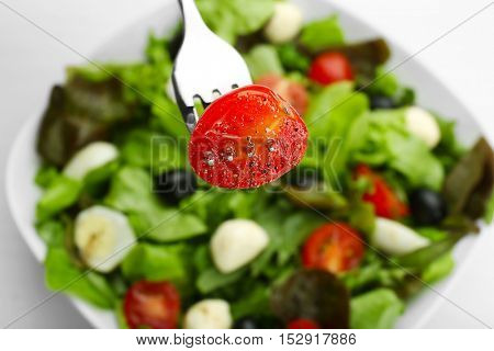 Slice of fresh tomato impaled on fork