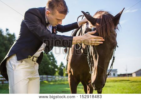 Portrait of happy man patting his horse on the nose, he is giving him alot of love and affection