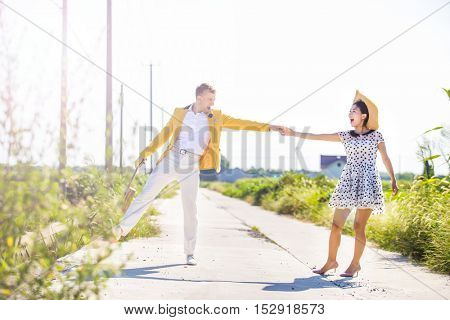 Full length of playful couple on footpath amidst field on sunny day