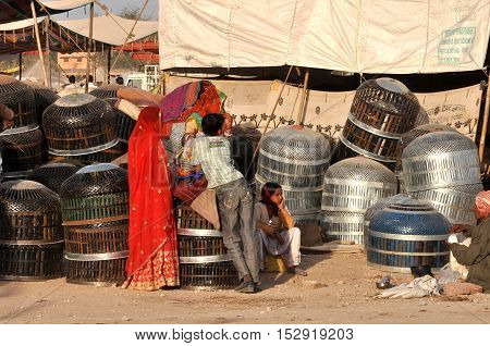 Naguar Rajasthan India- Febuary 10 2011: A family selling metal baskets to store utensils at Naguar Cattle Fair at Naguar Rajasthan India. Nagaur Cattle Fair (also known as Ramdeoji Cattle Fair) is held every year in the month of Jan-Feb in Nagaur distric