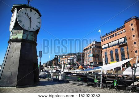 Clock tower on Aker Brygge Dock and modern building in Oslo Norway