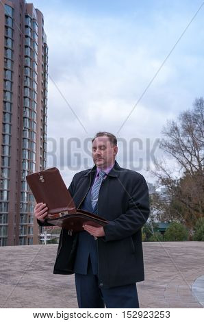 The man opened his briefcase next to a modern building