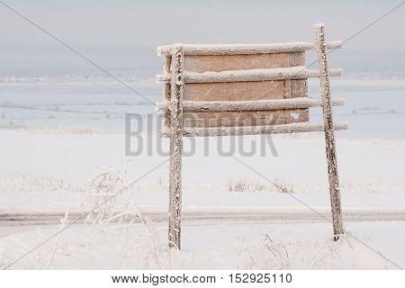Frozen bigboard with copyspace against winter landscape