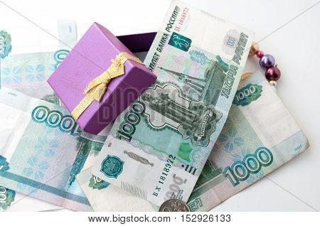 Thousandths bills and an open gift box with a bow