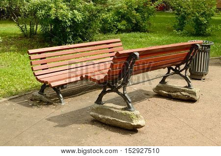 Two benches on the street set opposite to each other.