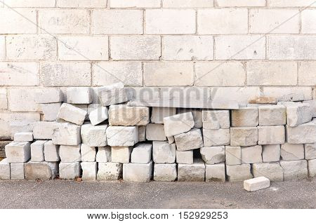 Blocks of lightweight cellular concrete on the brick wall background. The process of construction and insulation wall.