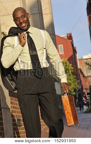 Confident African American businessman walking with briefcase in the city