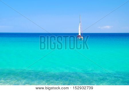 Seascape with blue sea water and a white sailboat.